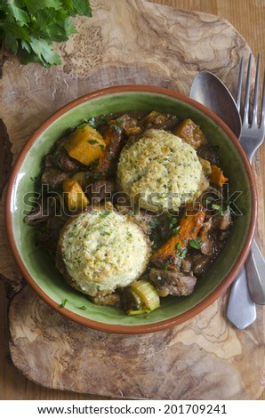 Tender slow-cooked beef with rich dark ale and dumplings - stock photo