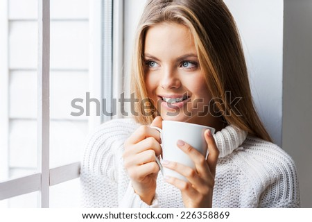 Tender softness. Beautiful young woman leaning the window at her apartment and holding a cup of coffee - stock photo