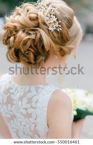 Tender wedding hairstyle. Long blond curly hair. Elegant collected hair. Bride wearing white dress with bouquet. Bridal stylish accessories.