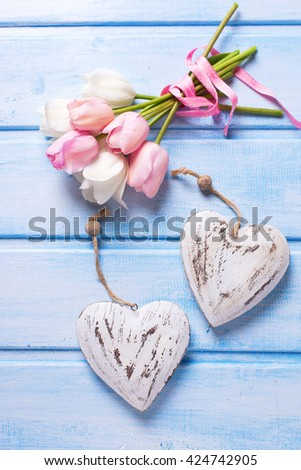 Tender white and pink spring tulips and two decorative hearts  on  blue wooden background. Pastel colors. Shabby chic. Selective focus.  - stock photo
