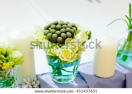 Tender white-green bouquet stands in a glass vase between candles - stock photo