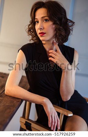 Tender young woman in a black dress with natural makeup and hairstyle