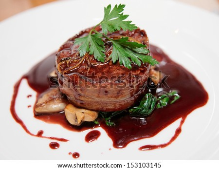 Tenderloin steak wrapped in bacon with demi-glace sauce - stock photo