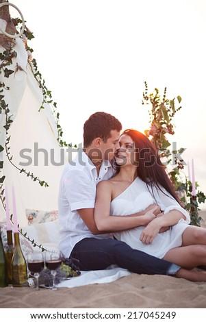 Tenderness couple on the beach picnic near wigwam - stock photo