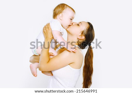 Tenderness, happy mother kiss baby - stock photo