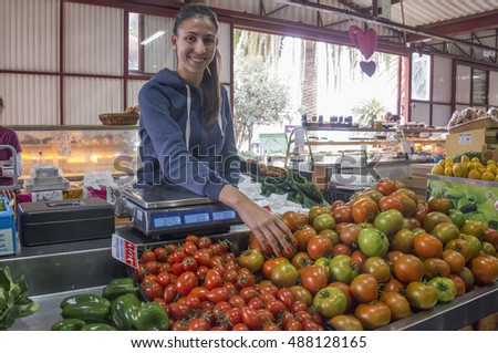 TENERIFE, CANARY ISLANDS - FEBRUARY 13, 2016: Young girl, selling vegetables in the agricultural market of the town of Tacoronte