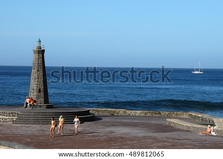 TENERIFE, CANARY ISLANDS - JANUARY 10, 2006: Bathers near the lighthouse of Bajamar on the north coast of the island