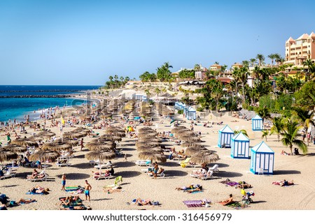 Tenerife, Canary Islands- January 1, 2015: People sunbathing in the picturesque El Duque beach, Tenerife. Canary islands, Spain - stock photo