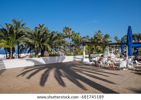 TENERIFE, CANARY ISLANDS - JANUARY 04, 2017: Terrace and palm trees on Colon Avenue, in the tourist city of Puerto de la Cruz, north of the island
