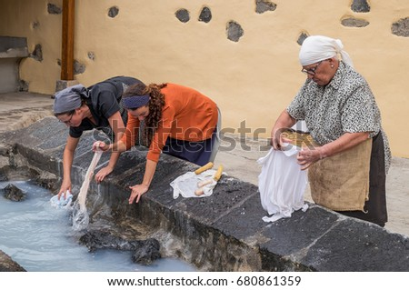 TENERIFE, CANARY ISLANDS - JUNE 04, 2017: Women washing clothes in a historical recreation realized in the Villa of the Orotava, to the north of the island