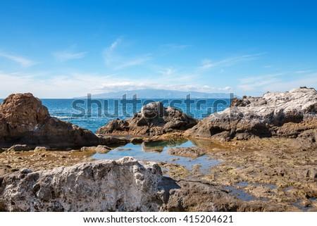 Tenerife coastal seascape with blue sea and La Gomera island in the distance. Canary Islands, Spain - stock photo