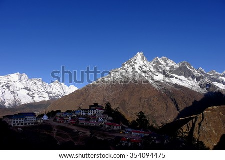 Tengboche in silhouette as sunrise lit Mt Khumbila along Everest Base Camp route, Khumbu, Nepal. Famed for its monastery and is a popular stopover for trekkers and climbers going to Everest Base Camp. - stock photo