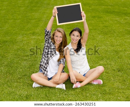 Tennage students sitting on the grass and holding a chalkboard - stock photo