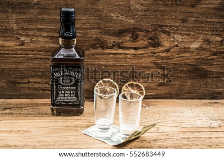 TENNESSEE, USA - NOVEMBER 14, 2016: Jack Daniel's Tennessee whiskey. brand of sour mash Tennessee whiskey that is highest selling American whiskey in the world. tip money and empty glasses. dry lemon