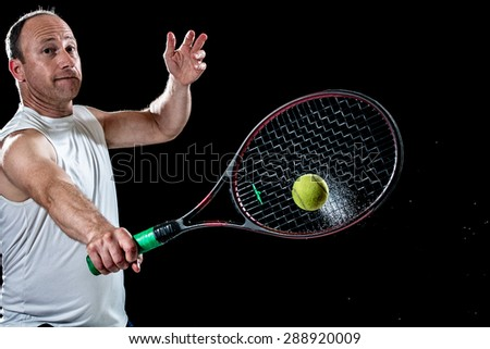 Tennis action shot. Backhand. Studio shot over black. - stock photo