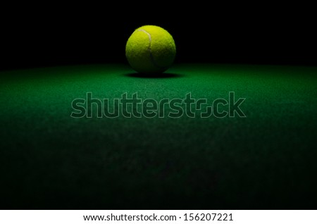 Tennis background - low key centered ball with green surface - stock photo