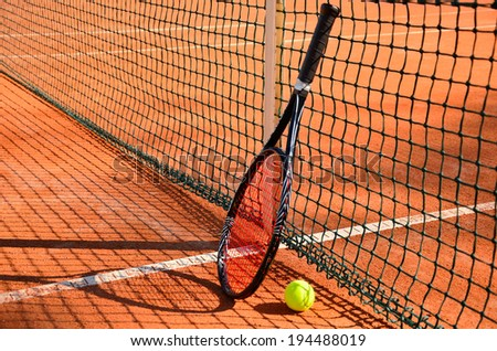 tennis ball and racket are near the net horizontal side view. net shadow - stock photo