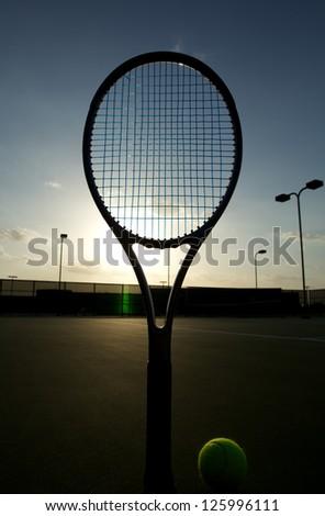 Tennis Ball and Racket Backlit at Sundown - stock photo