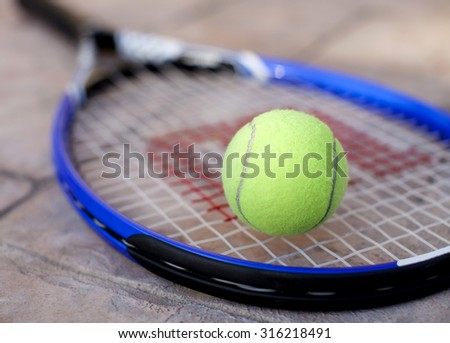 Tennis ball and racket on court