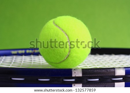 Tennis ball and racket on green background.