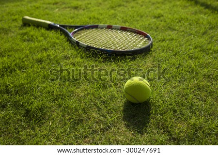 Tennis ball and racket on green grass field ground - stock photo