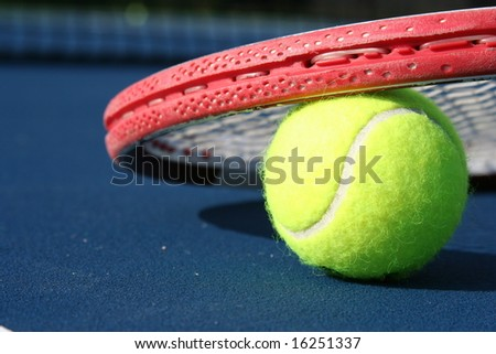 Tennis ball and racquet on a blue court - stock photo