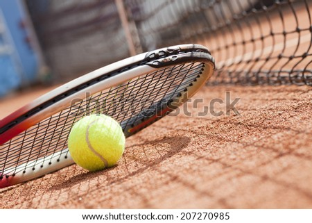 tennis ball and tennis racket on clay court - stock photo