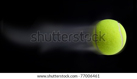 Tennis ball fast moving on black background leaving trail behind - stock photo