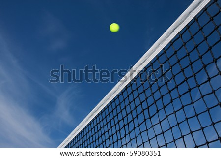 tennis ball flying over the net - stock photo