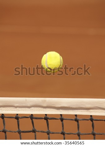 Tennis ball gliding over the net on clay court - stock photo