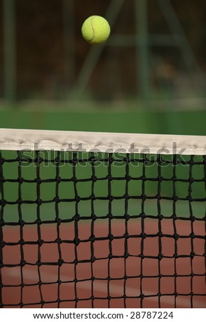 Tennis ball going over the net - stock photo