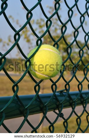 Tennis ball hit by power shot and stuck in fence