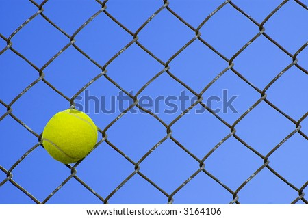 Tennis Ball in a Chain Link Fence