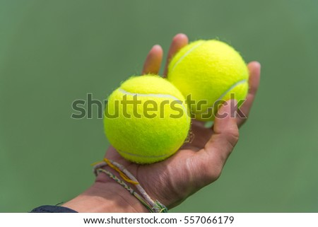 Tennis ball in hand.