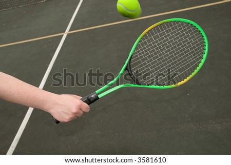 tennis ball in mid-flight with woman's hand and green racket - stock photo