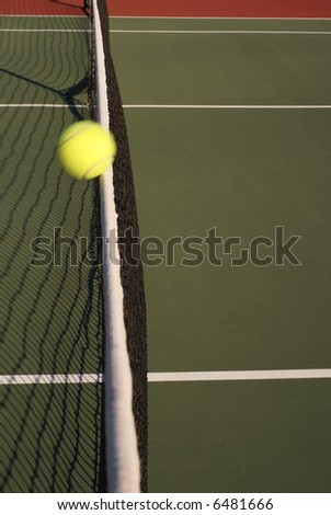 Tennis ball in motion hitting net - stock photo