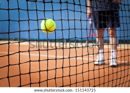 tennis ball in net - stock photo