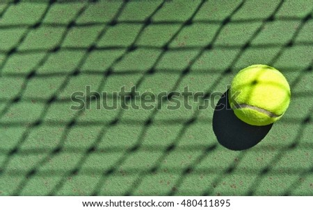 tennis ball in sunlight with net shadow pattern