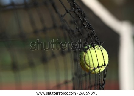 Tennis ball in the net - stock photo