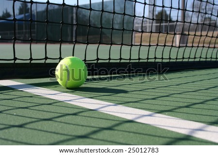 Tennis ball in the shadow if the court net