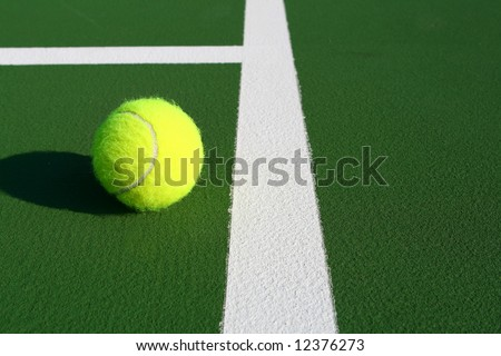 Tennis ball just inside the line - stock photo