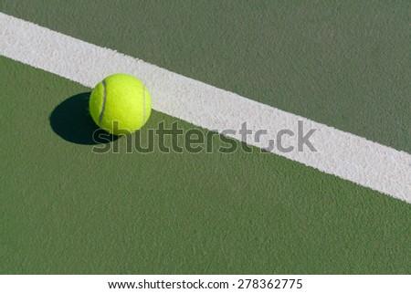 tennis ball next to line on hard court - stock photo