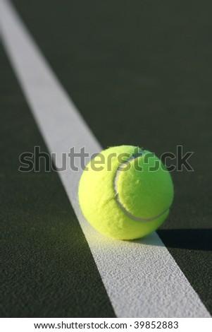 Tennis ball on a diagonal court line - stock photo