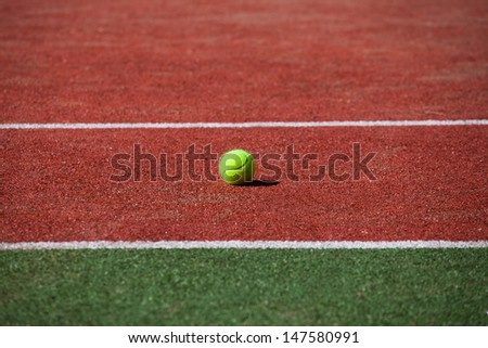 Tennis ball on a tennis court with copy space. - stock photo