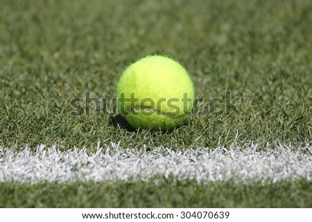 Tennis ball on grass tennis court - stock photo