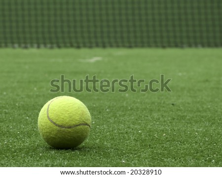 Tennis ball on synthetic grass of tennis court. - stock photo