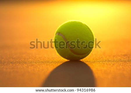 Tennis Ball on the Court Close Up at Sunset - stock photo
