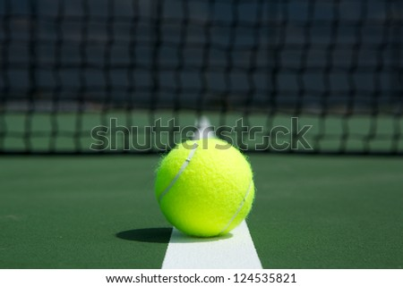 Tennis Ball on the Court Close up with the Net in the background - stock photo