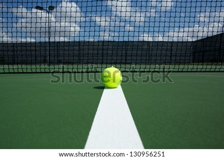 Tennis Ball on the Court Line with the Net in the background - stock photo