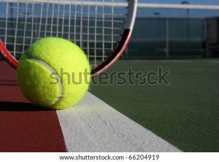 Tennis Ball on the court with racket in the background - stock photo